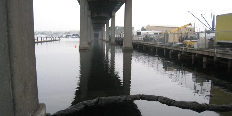 Image from the water looking down the length of the bridge with most bridge columns visible. Construction barge is in place on the right.